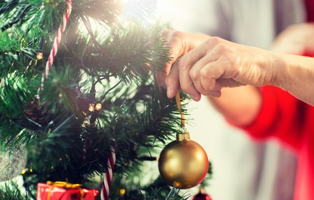Foto de holidays and people concept - close up of happy senior woman decorating christmas tree - Imagen libre de derechos