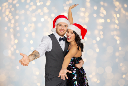 Photo for happy couple in santa hats at christmas party - Royalty Free Image