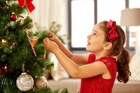 Foto de little girl decorating christmas tree at home - Imagen libre de derechos