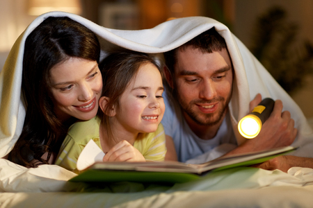 Photo pour happy family reading book in bed at night at home - image libre de droit