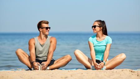 Foto de smiling couple stretching legs on beach - Imagen libre de derechos