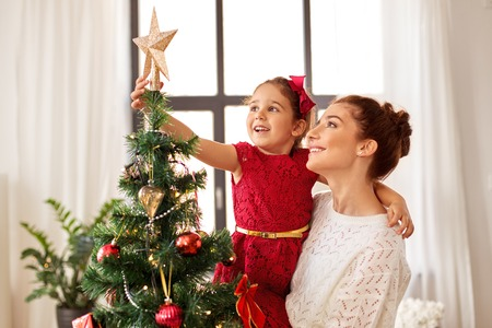 Photo pour mother and daughter decorating christmas tree - image libre de droit