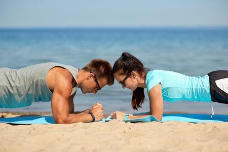 Foto de couple doing plank exercise on summer beach - Imagen libre de derechos