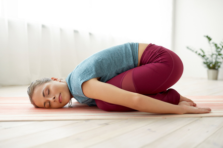 Foto de woman doing childs pose at yoga studio - Imagen libre de derechos
