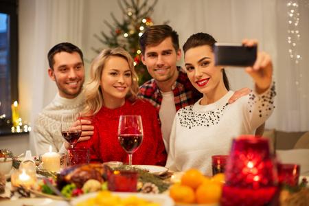 Foto de holidays and celebration concept - happy friends taking selfie by smartphone at home christmas dinner - Imagen libre de derechos