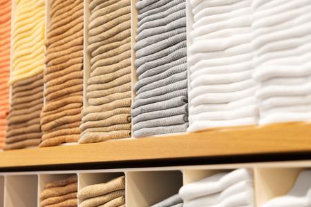 Photo pour close up of shelves with clothes at clothing store - image libre de droit