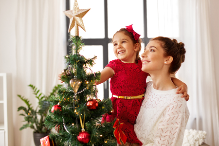 Foto de mother and daughter decorating christmas tree - Imagen libre de derechos