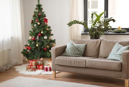 Foto de christmas tree, gifts and sofa at cozy home - Imagen libre de derechos