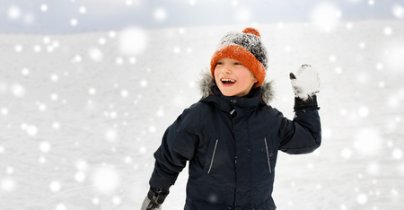 Photo for happy boy playing and throwing snowball in winter - Royalty Free Image