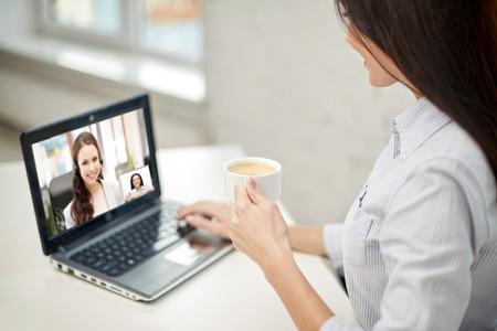 Foto de woman drinking coffee having video call on laptop - Imagen libre de derechos