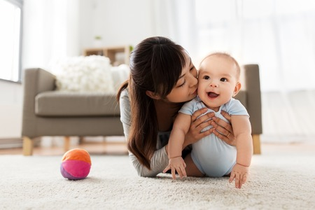Photo pour happy young mother kissing little baby at home - image libre de droit