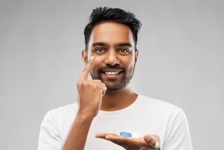 Foto de young indian man applying contact lenses - Imagen libre de derechos