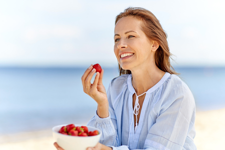 Foto de happy woman eating strawberries on summer beach - Imagen libre de derechos