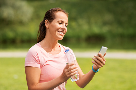 Photo pour woman with smartphone drinking water in park - image libre de droit
