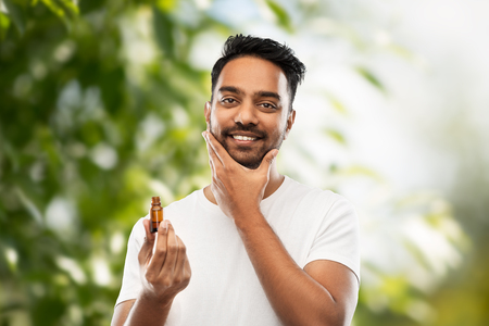 Photo pour indian man applying natural grooming oil to beard - image libre de droit