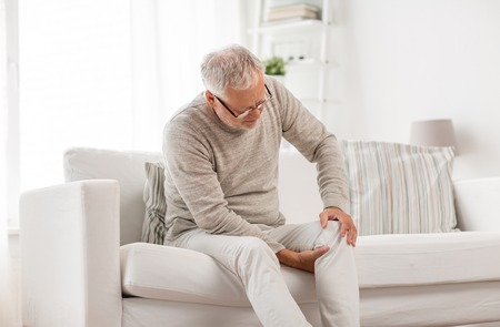 Photo pour senior man suffering from knee ache at home - image libre de droit