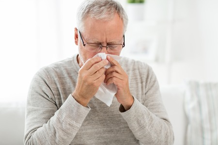 Foto de sick senior man with paper wipe blowing his nose - Imagen libre de derechos