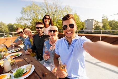 Photo pour happy friends taking selfie at rooftop party - image libre de droit