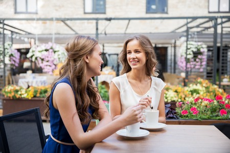 Photo for smiling young women drinking coffee at street cafe - Royalty Free Image