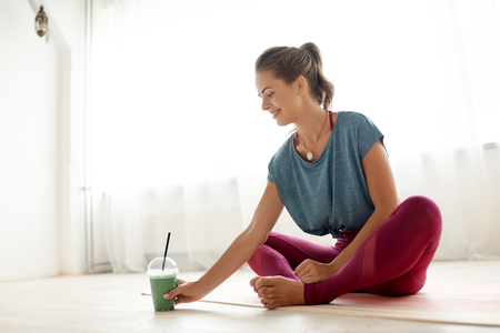 Foto de woman with cup of smoothie at yoga studio - Imagen libre de derechos