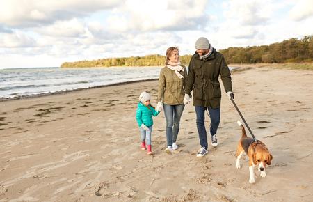 Photo pour happy family walking with beagle dog on beach - image libre de droit