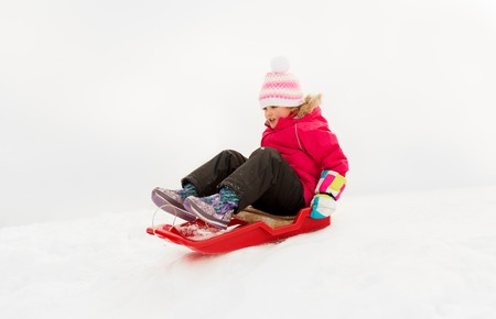 Photo for happy little girl sliding down on sled in winter - Royalty Free Image