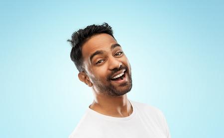 Photo pour young laughing indian man over blue background - image libre de droit