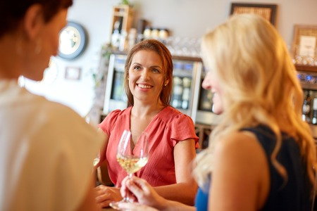 Photo pour happy women drinking wine at bar or restaurant - image libre de droit