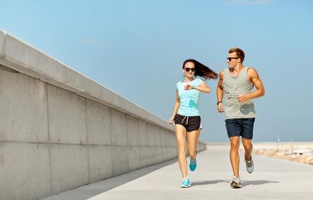 Foto de couple in sports clothes running outdoors - Imagen libre de derechos