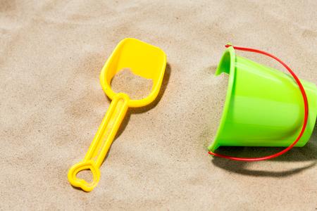 Foto de close up of toy bucket and shovel on beach sand - Imagen libre de derechos