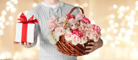 Photo for valentines day, people and greetings concept - close up of man holding basket full of flowers and gift box over festive lights background - Royalty Free Image