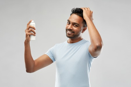 Photo for smiling indian man applying hair spray over gray - Royalty Free Image