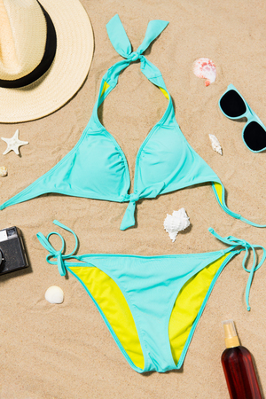 Photo for bikini, hat, camera and sunglasses on beach sand - Royalty Free Image