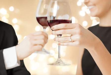 Photo pour close up of engaged couple drinking red wine - image libre de droit