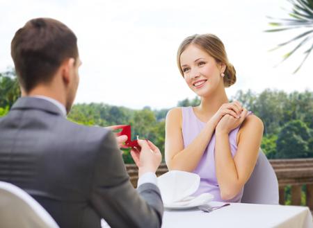 Photo pour man giving woman engagement ring at restaurant - image libre de droit