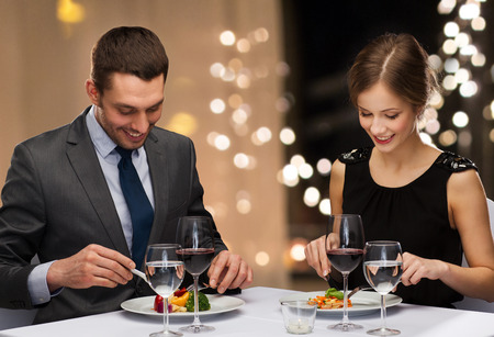 Photo pour smiling couple eating main course at restaurant - image libre de droit