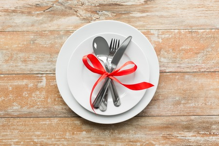 Photo pour cutlery tied with red ribbon on set of plates - image libre de droit