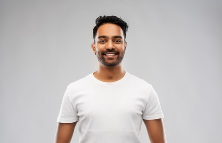 Photo pour smiling young indian man over gray background - image libre de droit