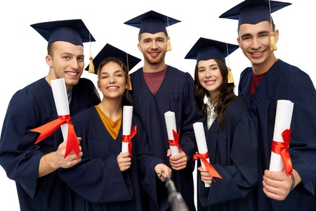 Photo pour happy graduates with diplomas taking selfie - image libre de droit