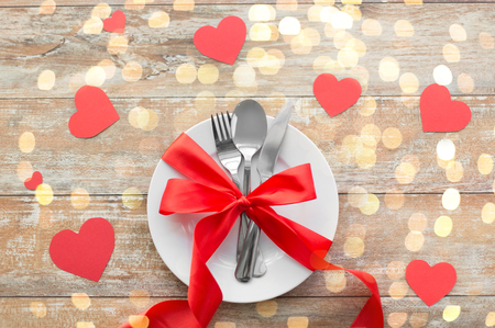 Photo pour valentines day, table setting and festive dinner concept - plate with spoon, knife and fork tied with red ribbon on wooden background decorated by paper hearts - image libre de droit