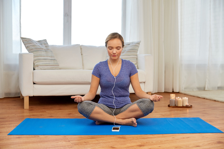 Photo for woman with music on smartphone meditating at home - Royalty Free Image