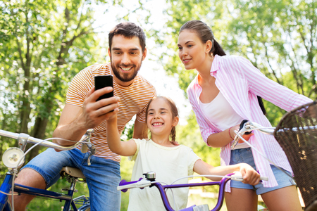 Foto de family with smartphone and bicycles in summer park - Imagen libre de derechos