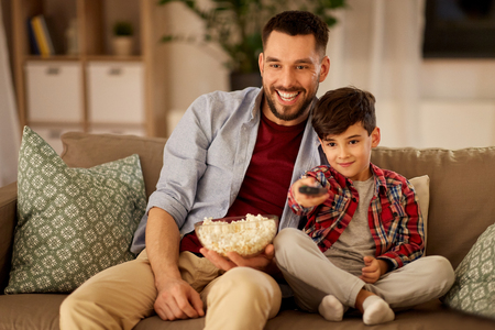 Foto de father and son with popcorn watching tv at home - Imagen libre de derechos