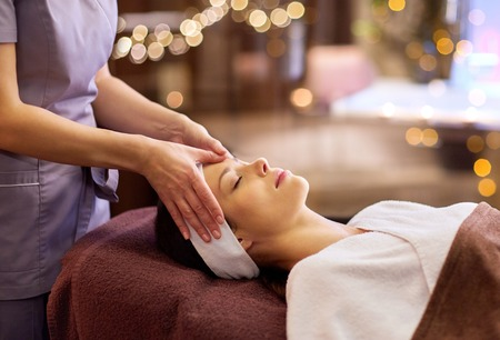 Photo pour people, beauty, lifestyle and relaxation concept - beautiful young woman lying with closed eyes and having face and head massage at spa - image libre de droit