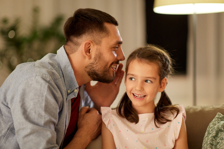Photo for happy father whispering secret to daughter at home - Royalty Free Image
