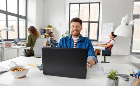 Foto de smiling creative man with laptop working at office - Imagen libre de derechos