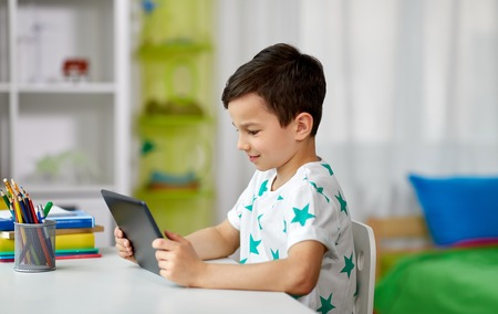 Photo pour student boy with tablet pc and notebook at home - image libre de droit