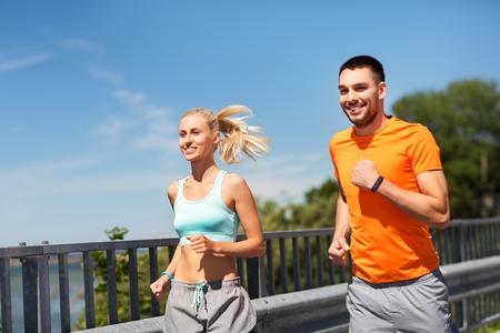 Foto de couple with fitness trackers running along bridge - Imagen libre de derechos