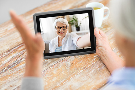 Foto de technology, communication and people concept - happy senior woman having video call with old friend on tablet computer at home - Imagen libre de derechos