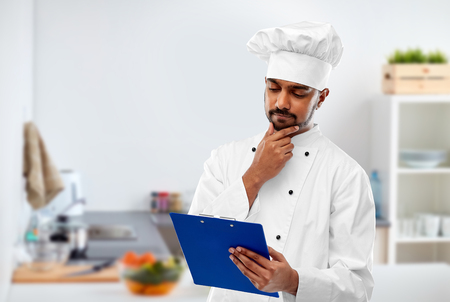 Foto de cooking, profession and people concept - male indian chef in toque reading menu on clipboard over kitchen background - Imagen libre de derechos